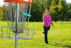 Throwing a disc. Woman throwing a disc to the disc basket Stock Photo