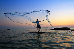 Throwing fishing net during sunrise stock photography