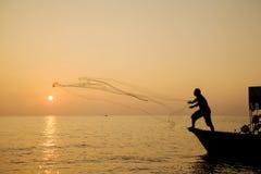 Throwing fishing net at sunrise Royalty Free Stock Images