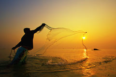 Throwing fishing net during sunset Royalty Free Stock Photography