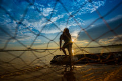 Throwing fishing net. Sunset Asia stock photography