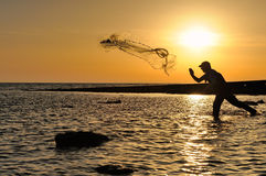 Throwing fishing net during sunset Stock Photos