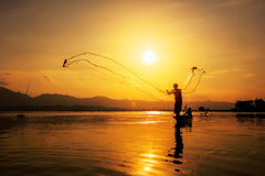 Throwing fishing net during sunset. At Kwan Phayao of Thailand stock images