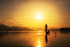 Throwing fishing net during sunset Royalty Free Stock Image