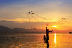 Throwing fishing net during sunset Royalty Free Stock Photo