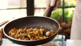 Throwing food in a pan. Chef frying mushrooms
