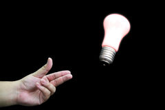 Throwing an idea. A photo of a hand throwing a light bulb with black background Stock Images