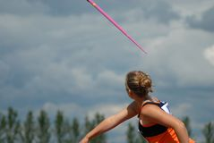 Throwing Javelin. Young pretty female teen throws javelin in competition. Copy Space Stock Images