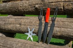 Throwing knife and Shuriken throwing star, on wooden backgroun stock images