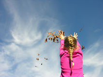 Throwing leaves. A young girl throwing leaves up into the air and catching them Royalty Free Stock Photography