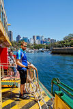 Throwing the line. SYDNEY,AUSTRALIA - OCTOBER 19,2014: A deckhand prepares to throw the mooring rope as one of Sydney's iconic ferries approaches Neutral Bay stock images