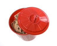 Throwing Money Away: Bills in Garbage Can. US Currency One Hundred Dollar Bills inside of a red garbage can with a lid next to it.   isolated on white background Royalty Free Stock Images