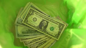 Throwing money away, dollars Fall in green Trash Can basket, freedom from finance, wasting money. Throwing money away, dollars Fall in Trash Can basket, freedom stock video footage