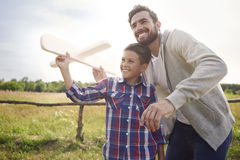 Throwing paper plane. Father and son testing a paper plane royalty free stock photography
