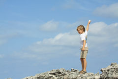 Throwing pebbles. Boy throwing pebbles into the air on the beach Stock Photo
