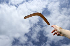 Throwing plain boomerang, midair. Throwing a plain wooden boomerang midair with blue sky and cloud background royalty free stock photography