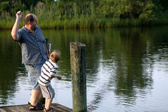Throwing Rocks. A father and son throwing rocks from a pier Royalty Free Stock Images
