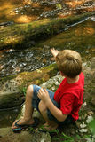 Throwing Rocks. A little boy throwing rocks into a stream Royalty Free Stock Photography