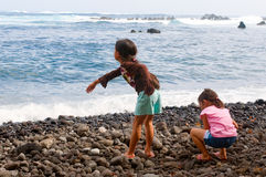 Throwing Rocks. Two young asian girls throwing rocks into the ocean Royalty Free Stock Photos