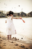 Throwing sands. Two year old girl dressed in white throwing sands in the water Stock Photography