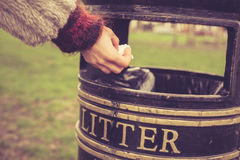 Throwing something in the litter. A woman is throwing something in a litter bin at the park stock images