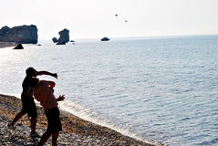 Throwing stones in the sea. Two young men throwing stones in the water Royalty Free Stock Photo