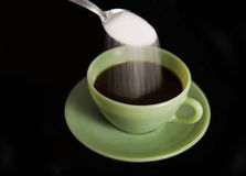 Throwing sugar in a cup of coffee Royalty Free Stock Images