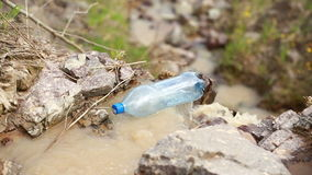 The thrown bottle floats in the river stock footage