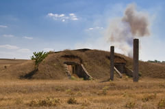 The thrown bunker. The old thrown bunker in a military part and a smoke in steppe Stock Photo