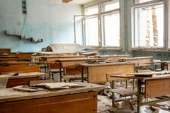 The thrown and destroyed school in Pripyat after the Chernobyl accident in Ukraine in 1986. School desks and scattered textbooks. The thrown and destroyed soviet royalty free stock photo