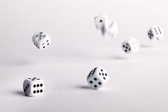 Thrown dice bouncing across a white surface Royalty Free Stock Image