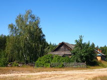 The thrown house. At the dirt sandy road of a birch around the blue sky summer Stock Photography