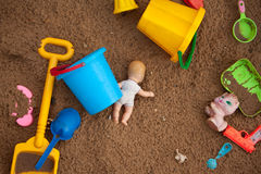 The thrown toys in a sandbox. The thrown toys in a brown sandbox Royalty Free Stock Photos