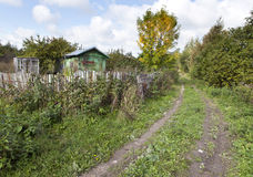 The thrown wooden house and dirt road in rural areas Stock Images
