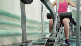 Thrust of the upper block. The girl is doing exercises on the simulator in the gym. 1080 stock video footage