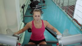 Thrust of the upper block. The girl is doing exercises on the simulator in the gym. The muscles of the back. Thrust of the upper block. The girl is doing stock video footage