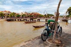 Thu Bon riverbank in Hoi An, Vietnam, met driewieler in de voorgrond in de dag royalty-vrije stock fotografie