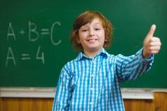 Thub sorridente felice di manifestazione del ragazzo su sul fondo della lavagna Concetto della scuola ed educativo Fotografia Stock