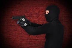 Thug with gun and flashlight Stock Photo
