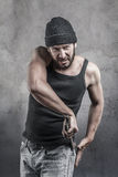 Thug preparing to use a wrench as a weapon. Pulling it out of the pocket of his jeans as he watches the camera with a dangerous angry expression, over a Royalty Free Stock Images