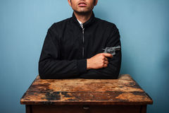 Thug at table with gun. Thug at table with a gun Royalty Free Stock Photo