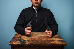 Thug at table with gun and knife Stock Photography