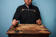 Thug at table with nunchucks Stock Photography