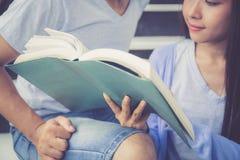 Thuis boeken de Aziatische knappe man van het close-uppaar en de mooie vrouwenlezing en blij Stock Foto