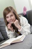 Thuis en meisje dat ontspant leest Stock Afbeelding