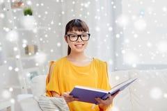 Thuis glimlachend het jonge Aziatische boek van de vrouwenlezing Royalty-vrije Stock Foto's