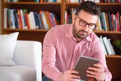 Thuis lezend een nieuwe best-seller op tabletlezer royalty-vrije stock afbeelding