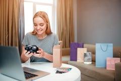Thuis online winkelend De jonge die blondeklant is gelukkig over manieraankoop, door Internet wordt bevolen en wordt geleverd royalty-vrije stock foto's