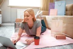 Thuis online winkelend De jonge gelukkige klant bekijkt laptop en kiest goederen in online winkel terwijl het liggen op stock fotografie