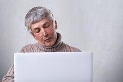 Thuis surfend netto Peinzende rijpe mens die oogglazen en toevallige sweater dragen die een boek op zijn laptop lezen terwijl het stock foto's